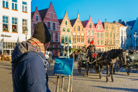 horse drawn carriage: Bruges, Belgium - December 28, 2014: Street artist paints a picture of a Horse carriage waiting tourists on Grote Markt square of Brugge Christmas. Bruges is UNESCO world heritage listed for its medieval center.