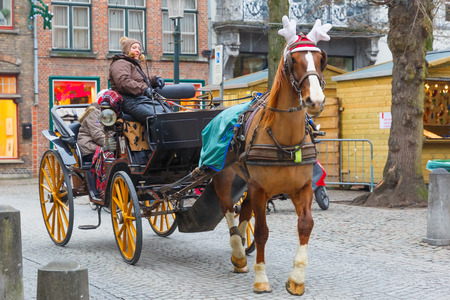 brugge: Bruges, Belgium - December 26, 2014: Horse carriage on the street of Brugge Christmas. Belgian city of Bruges is UNESCO world heritage listed for its medieval center.