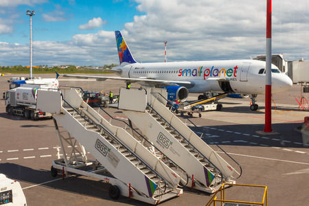 may fly: Vilnius, Lithuania - May 2, 2014: Preparation of aircraft Small Planet Airlines to fly, loading baggage, refueling at Vilnius airport