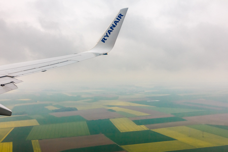 scheduled: Vilnius, Lithuania - May 2, 2014: Looking through window aircraft Ryanair during flight in wing. Ryanair is one of the largest low-cost European airline by scheduled passengers carried.