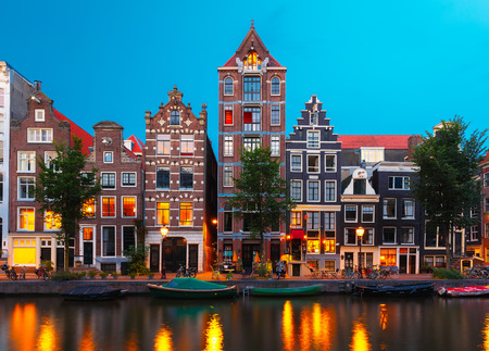 dutch typical: Night city view of Amsterdam canal Herengracht, typical dutch houses and boats, Holland, Netherlands.