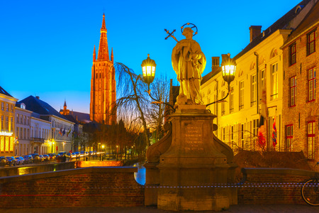 Cityscape with canal Dijver, Bridge St. Nepomuk and a Church of Our Lady in Bruges photo