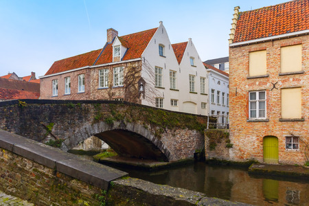 Green canal and bridge in Bruges, Belgium photo