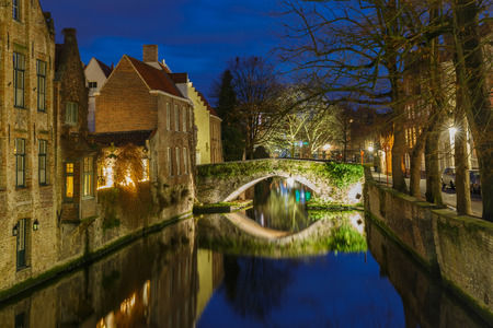 brugge: Cityscape with a Green canal in Bruges at night