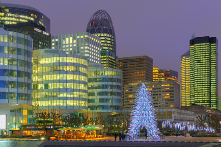 Paris, France - December 19, 2014: Christmas tree among the skyscrapers of La Defense.  Defense - Parisian Manhattan, the largest business center in Europe.