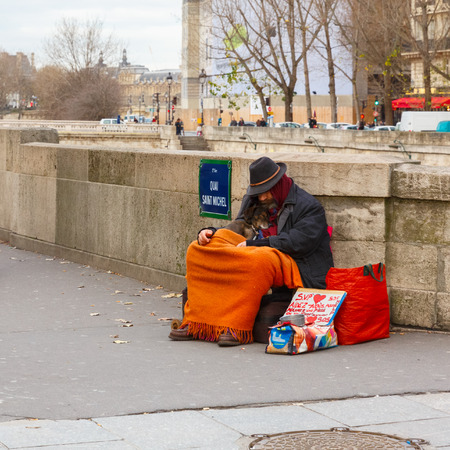 Paris, France - December 20, 2014: Clochard, homeless with dog in winter on the Paris waterfront 報道画像