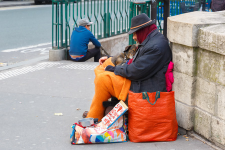 hobo: Paris, France - December 20, 2014: Clochard, homeless with dog in winter on the Paris waterfront Editorial
