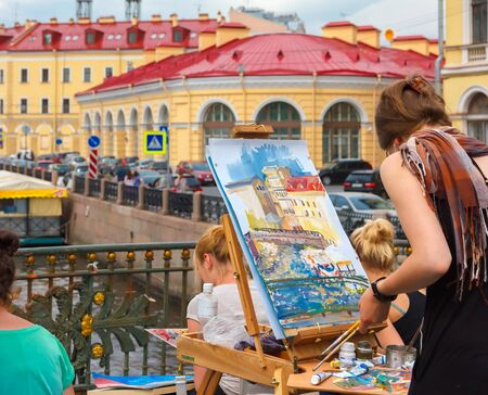 draw bridge: St. Petersburg, Russia - June 10, 2013: Young artists draw river landscape on the bridge over the Neva River.