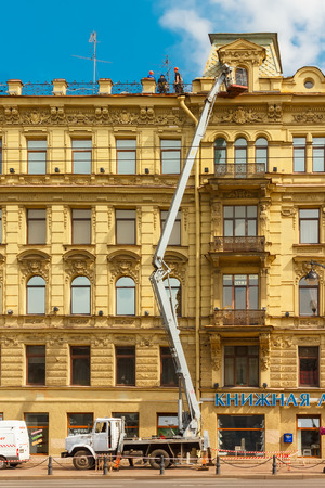 furnish: St. Petersburg, Russia - June 10, 2013: Construction workers on scaffolding near a facade of an ancient building for restoration. Editorial