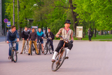 Vilnius, Lithuania - May 1, 2014: Unusual man in top hat rides on creative retro bike and the surprised young modern cyclists look at him