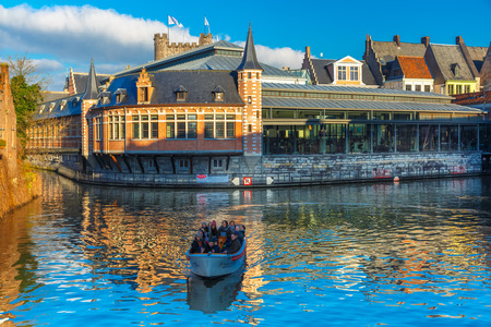 gent: Ghent, Belgium - December 29, 2014: Tourist boat on the river Leie near picturesque medieval houses. Ghent - one of the most beautiful cities in Europe, a popular tourist center.