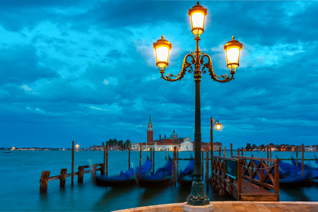 Gondolas at twilight in Venice lagoon Italia