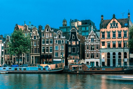 Night city view of Amsterdam canal, typical dutch houses and boats, Holland, Netherlands.. Toning in cool tones