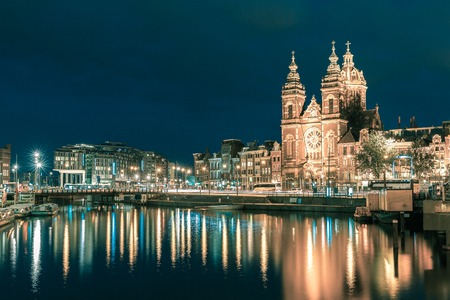 city at night: Night city view of Amsterdam canal and Basilica of Saint Nicholas, Holland, Netherlands. Long exposure.. Toning in cool tones