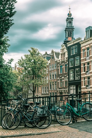 westerkerk: City view of Amsterdam canal, church Westerkerk and typical houses, boats and bicycles, Holland, Netherlands... Toning in cool tones Stock Photo