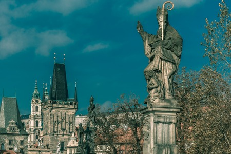 st charles: Sculpture of St Augustine with a burning heart in hand trampling heretical books on Charles Bridge in Prague, Czech Republic. Toning in cool tones