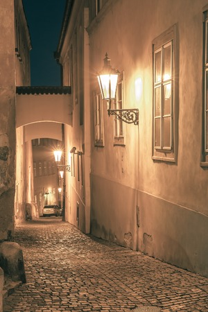 cobbled: Narrow cobbled street of the old town at night in Mala Strana, Prague, Czech Republic. Toning in cool tones Stock Photo