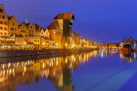 gdansk: Old harbour crane and city gate Zuraw in old town of Gdansk, Dlugie Pobrzeze and Motlawa River at night, Poland