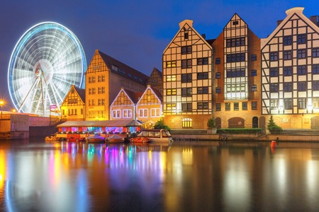 trade fair: Ferris wheel with water reflection at Trade fair St Dominic in Old Town of Gdansk at night, Poland Stock Photo