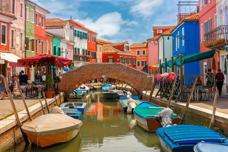 lagoon: Bridge and canal with colorful houses on the famous island Burano, Venice, Italy