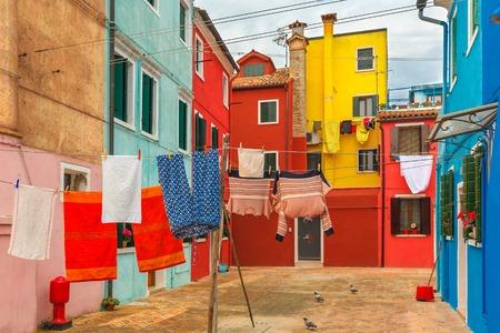 lavanderia: Patio con casas de colores con secado de la ropa en una cuerda en la famosa isla de Burano, Venecia, Italia