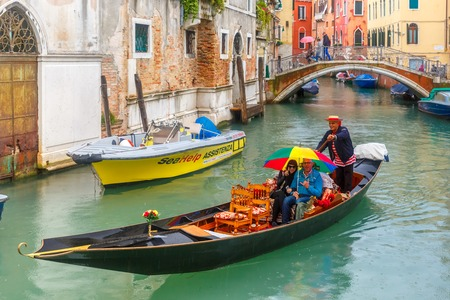 ferro: Venice, Italy - May 23, 2015: Happy tourists under bright umbrella ride in Gondola on canal in the rain. Gondola, the symbol of Venice, is a traditional Venetian rowing boat. Now there are 425 hereditary Venice gondoliers with their own courts.