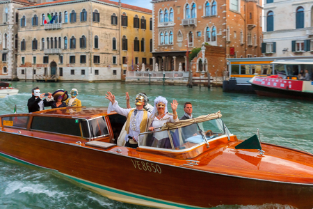 ferro: Venice, Italy - May 23, 2015: Happy people in fancy dress ride on a boat on the Grand Canal.