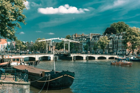 amstel: City view of Amsterdam canal Amstel, bridge Magere Brug, boat and bicycles, Holland, Netherlands.. Toning in cool tones Stock Photo