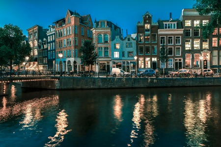 amsterdam: Night city view of Amsterdam canal, typical dutch houses and bridge, Holland, Netherlands.. Toning in cool tones