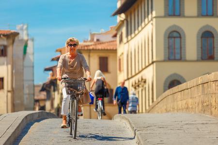 trinita: Florence, Italy - May 19, 2015: Elderly Caucasian woman cyclist on the Bridge of Santa Trinita over river Arno, Tuscany.