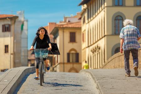 trinita: Florence, Italy - May 19, 2015: Young Asian girl cyclist on the Bridge of Santa Trinita over river Arno, Tuscany.
