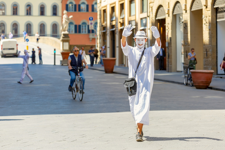 trinita: Florence, Italy - May 19, 2015: Street actor in a white dress, gloves, hat and a white mask of a clown near the Bridge of Santa Trinita over river Arno, Tuscany. Editorial