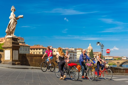 trinita: Florence, Italy - May 19, 2015: Cyclists on the Bridge of Santa Trinita over river Arno, Tuscany. Editorial