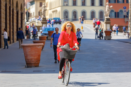 trinita: Florence, Italy - May 19, 2015: Caucasian woman cyclist near the Bridge of Santa Trinita over river Arno, Tuscany. Editorial