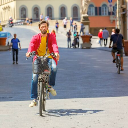 trinita: Florence, Italy - May 19, 2015: Caucasian man cyclist near the Bridge of Santa Trinita over river Arno, Tuscany. Editorial