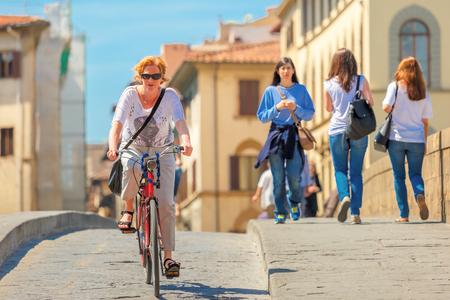 trinita: Florence, Italy - May 19, 2015: Caucasian woman cyclist on the Bridge of Santa Trinita over river Arno, Tuscany.