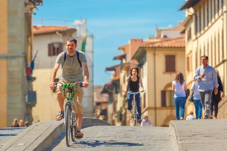 trinita: Florence, Italy - May 19, 2015: Caucasian man cyclist on the Bridge of Santa Trinita over river Arno, Tuscany. Editorial