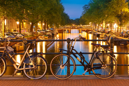 house gables: Night  illumination of Amsterdam canal and bridge with typical dutch houses, boats and bicycles, Holland, Netherlands.
