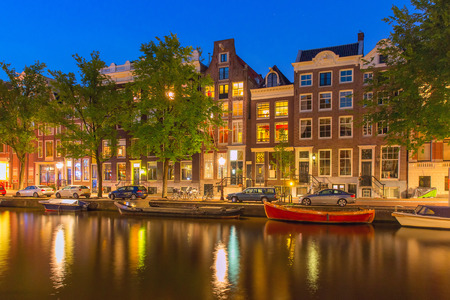 city view: Night city view of Amsterdam canal Herengracht, typical dutch houses and boats, Holland, Netherlands.