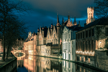 belfort: Scenic cityscape with a medieval tower Belfort and the Green canal, Groenerei,  at sunset in Bruges, Belgium. Toning in cool tones Stock Photo