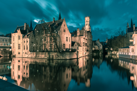 belfort: Scenic cityscape with a medieval fairytale town and tower Belfort from the quay Rosary, Rozenhoedkaai, at sunset in Bruges, Belgium. Toning in cool tones