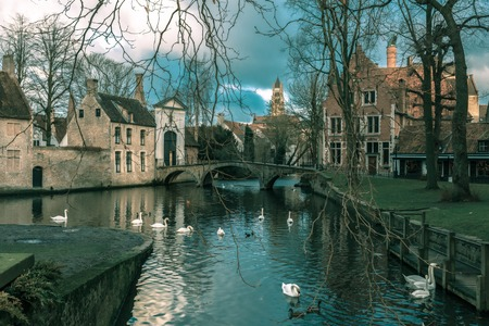 city center: Landscape at Lake Minnewater with church and bridge in Bruges, Belgium. Toning in cool tones Stock Photo