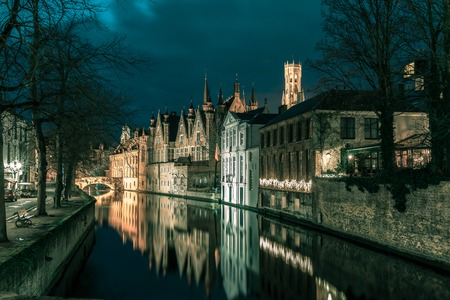 belfort: Scenic night cityscape with a medieval tower Belfort and the Green canal, Groenerei, in Bruges, Belgium. Toning in cool tones