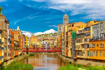 saint mary: Colorful yellow and orange houses and Eiffel Bridge, Old fish stalls, reflected in water river Onyar, in Girona, Catalonia, Spain. Saint Mary Cathedral at background.