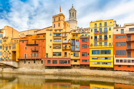 saint mary: Colorful yellow, red and orange houses with the Catalan flag reflected in water river Onyar, in Girona, Catalonia, Spain. Saint Mary Cathedral at background.