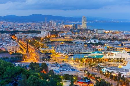 colom: Aerial view over Port Vell marina, Passeig de Colom, Barceloneta and Rambla de Mar at night in Barcelona, Catalonia, Spain