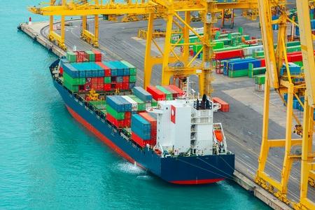 Charge de conteneurs sur un cargo de la mer, vue sur le port de fret et de terminal à conteneurs de Barcelone, avec la colline de Montjuic, Barcelone, Catalogne, Espagne.