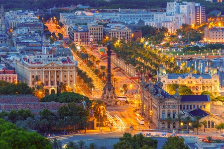 Aerial view over square Portal de la pau, and Port Vell marina and Columbus Monument at night in Barcelona, Catalonia, Spain