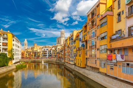 Kleurrijke gele en oranje huizen en de brug Pont de Sant Agusti weerspiegeld in het water rivier Onyar, in Girona, Catalonië, Spanje. Kerk van Sant Feliu en Saint Mary Kathedraal op de achtergrond. Stockfoto