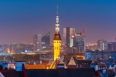 office building: Night aerial cityscape with old town hall spire and modern office buildings skyscrapers in the background in Tallinn, Estonia